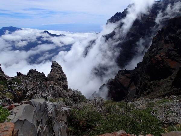 Wolken die als een waterval de berg op waaien